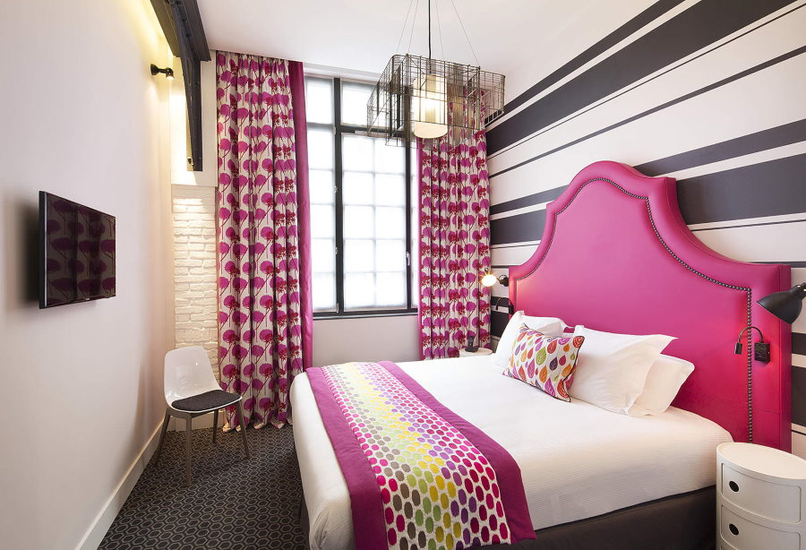 Узкая спальная комната с яркой кроватью