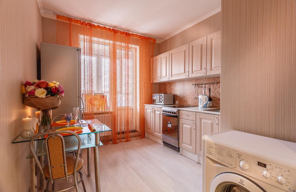 Красная кисея на балконном окне кухни