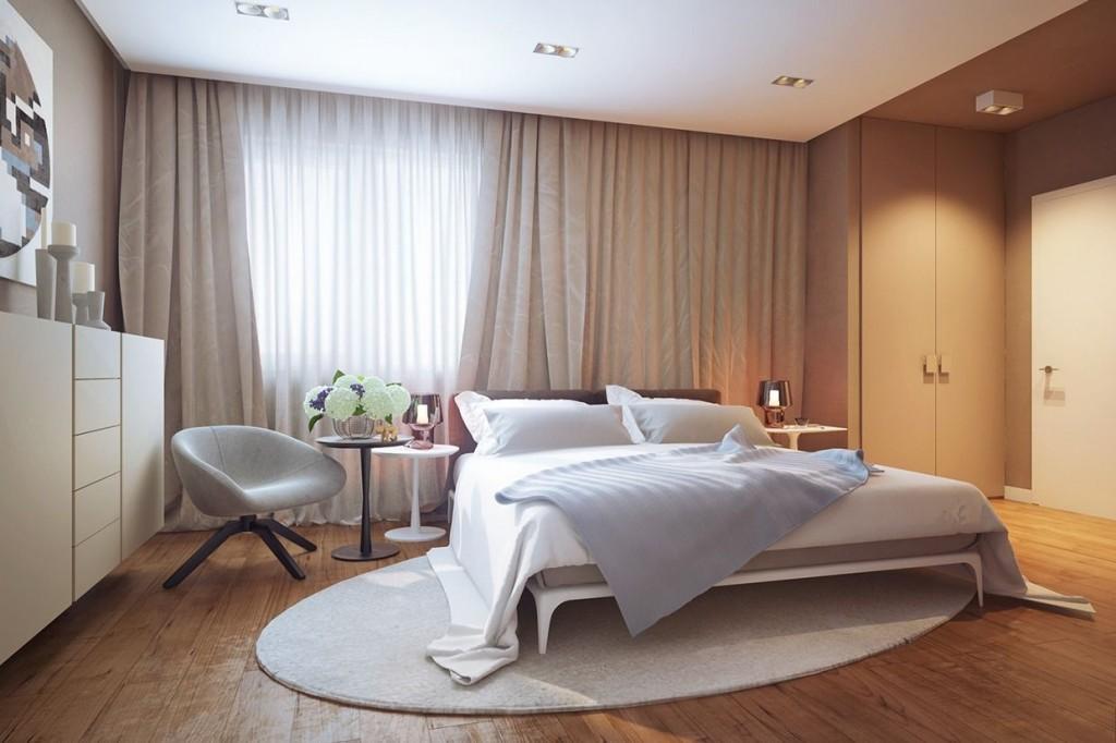 Овальный коврик в спальне с широкой кроватью