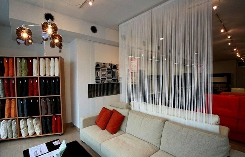 Белые нитяные шторы за спинкой дивана в квартире