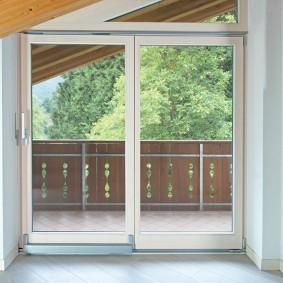 Стеклянные двери на балконе в мансардной комнате