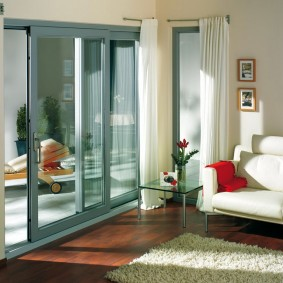 Гостиная комната с алюминиевыми дверями на балконе