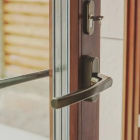 Стильная ручка на деревянной двери балкона
