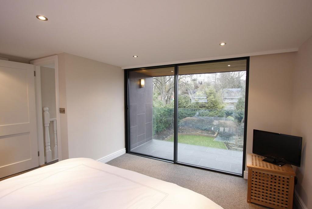 Панорамное раздвижное окно из стекла в спальне
