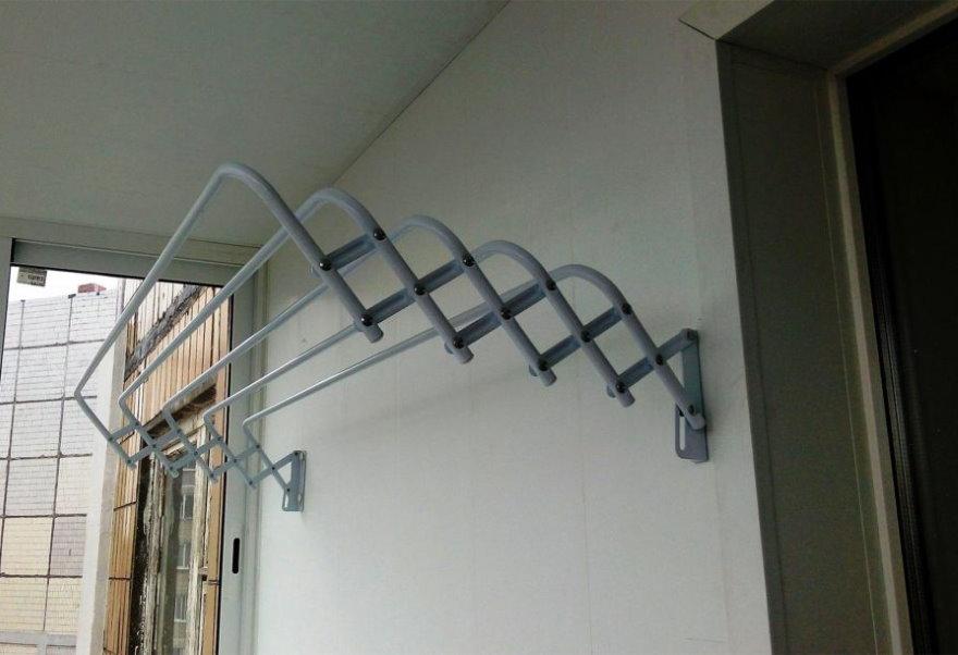 Выдвижная сушилка для белья на стене балкона