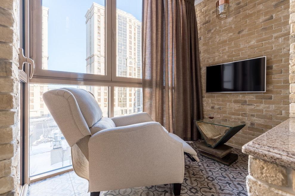 Удобное кресло в зоне отдыха на балконе