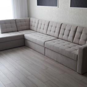 Г-образный диван в углу гостиной комнаты
