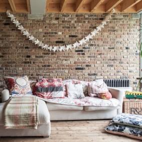 Светлый диван в гостиной с кирпичной стеной