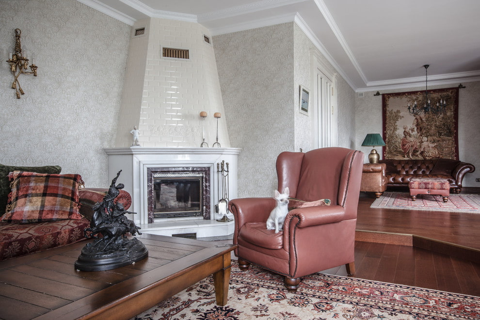 Угловой камин в гостиной комнате с кожаным креслом