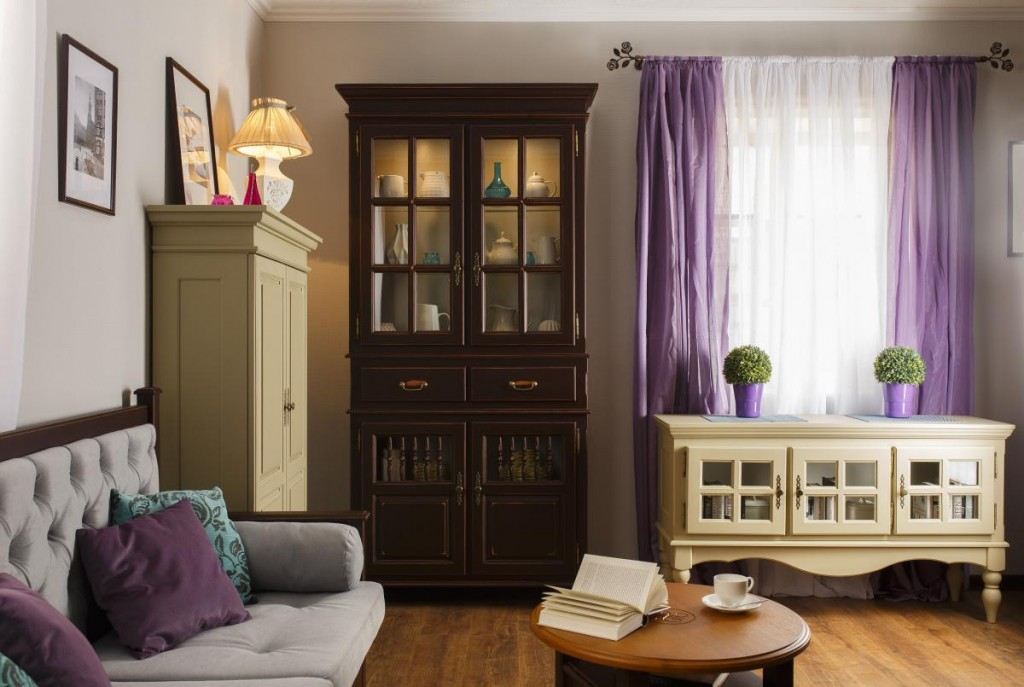 Узкий сервант-буфет в гостиной с фиолетовыми шторами