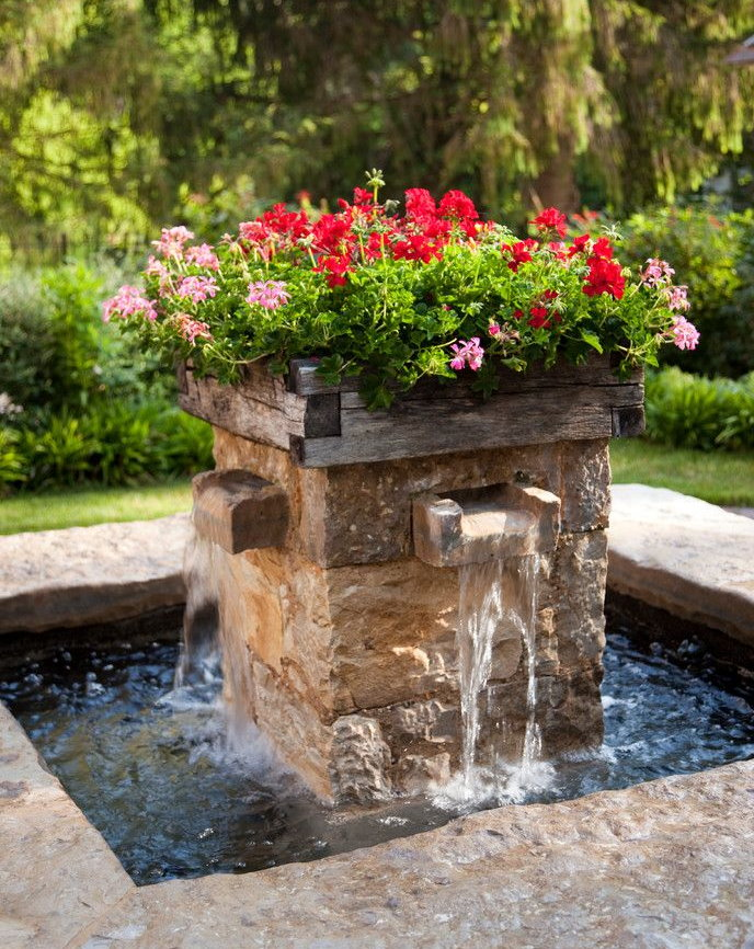 Каменный фонтан с цветами наверху