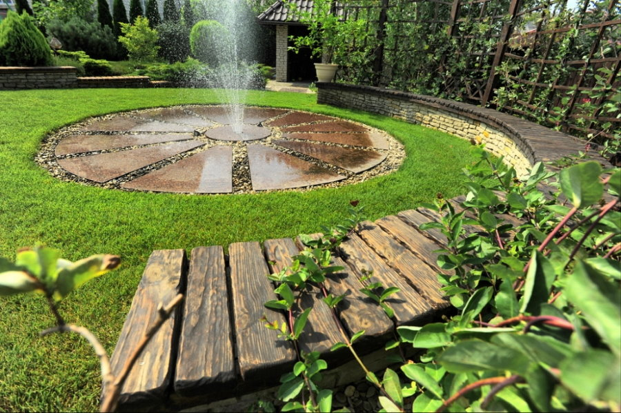 Деревянная лавочка вокруг садового фонтана