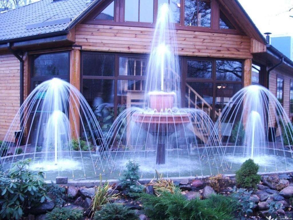 Шикарные фонтаны перед деревянным домом