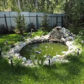 Декоративный пруд на участке с забором из профлиста