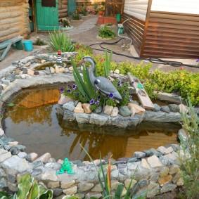Статуя цапли на берегу садового прудика