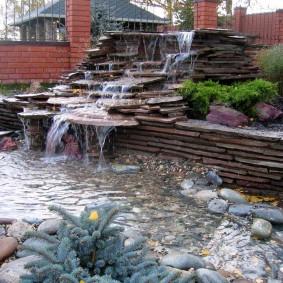 Каскадный водопад на участке с кирпичной оградой