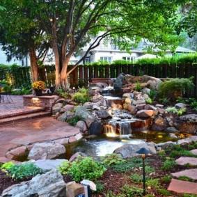 Декоративный водопад в саду с высокими деревьями