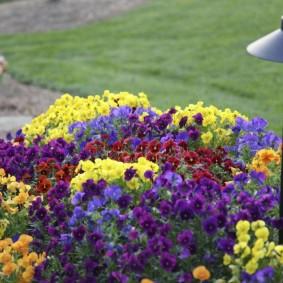 Садовый фонарик на цветочной клумбе