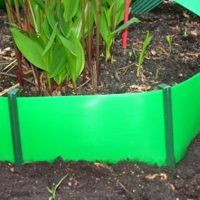 Бордюр на клумбе из зеленого пластика