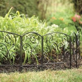 Кованное ограждение на клумбе с растениями