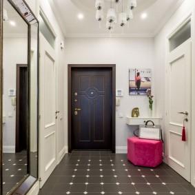 Розовый пуф перед дверью в прихожей