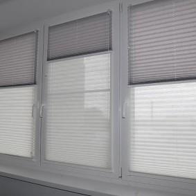 Двойные шторы плиссе на окне балкона