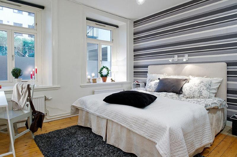 Белая кровать в спальне с полосками на обоях
