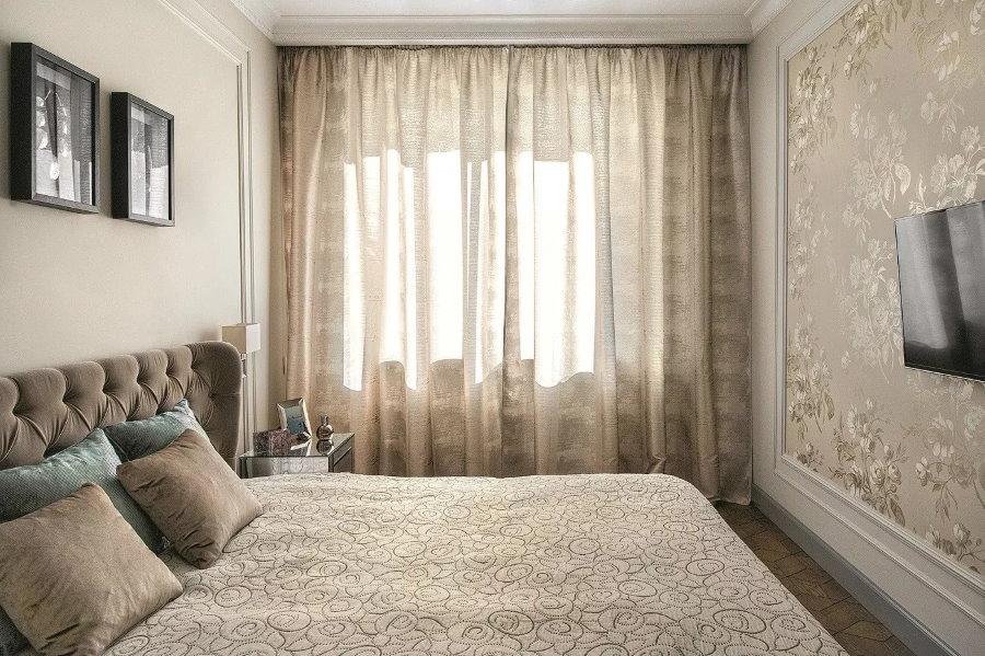 Интерьер маленькой спальни с телевизором на стене