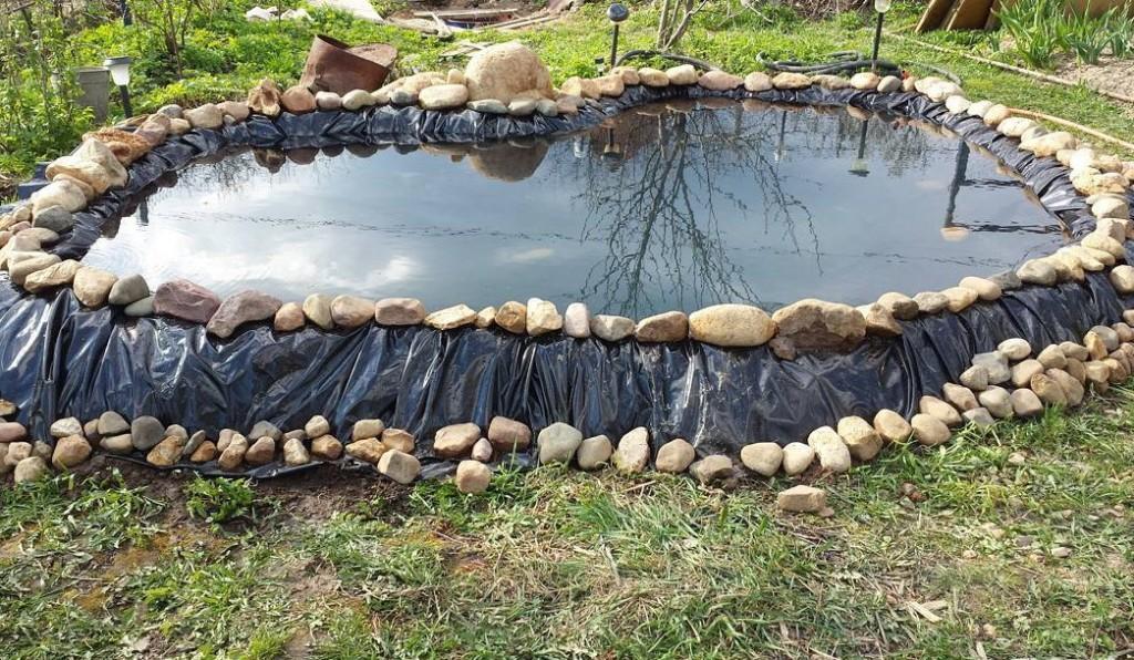 Закрепление камнями пленки на берегу водоема