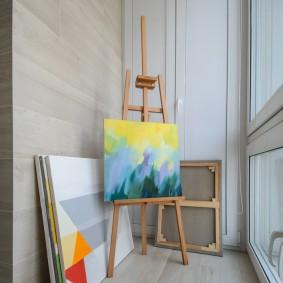 Мольберт художника на лоджии с панорамным окном