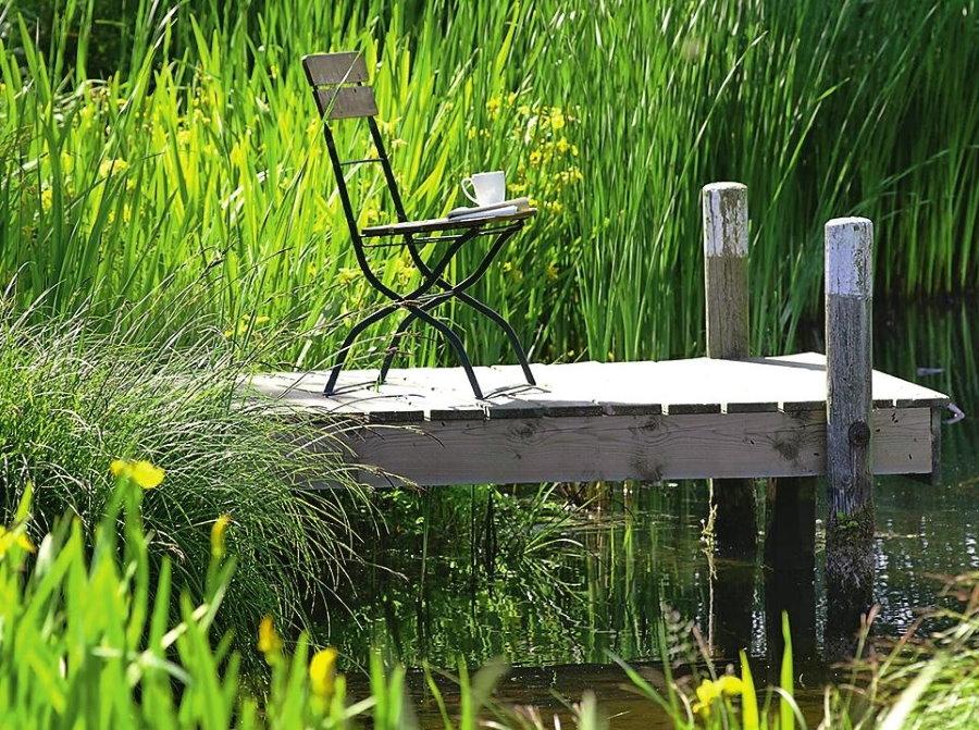 Складной стульчик на деревянном мостике у пруда