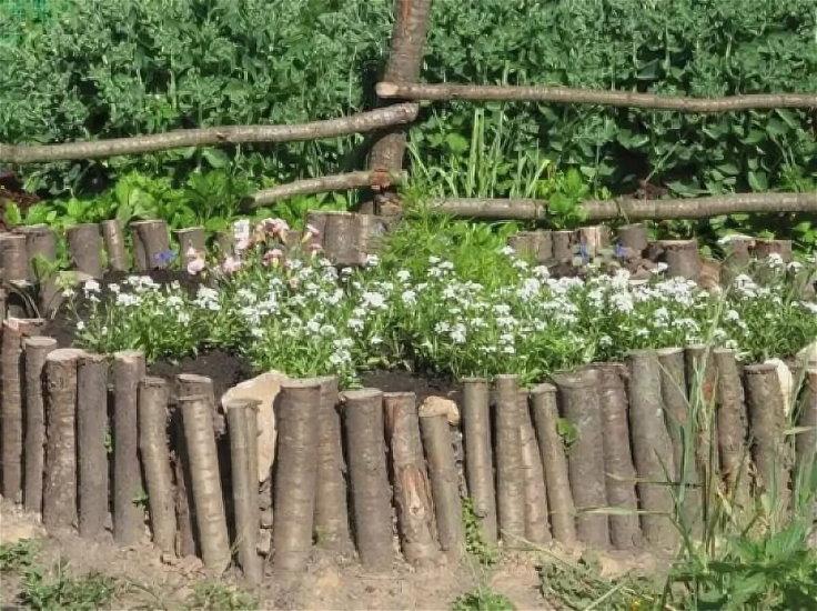 Бордюр из веток вокруг клумбы с цветами