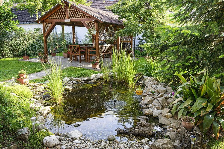 Деревянная беседка около пруда в саду