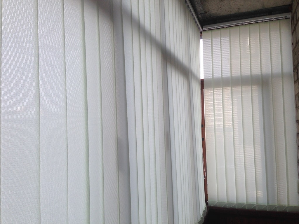 Светлые тканевые шторы на небольшом балконе