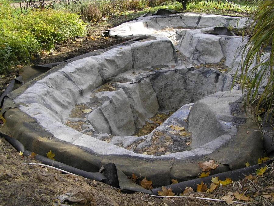 Укладка синтетического каучука в котлован для пруда