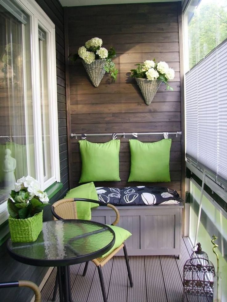 Зеленые подушки на спинке балконного диванчика