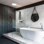 Черно-белая ванная комната с мраморными подиумом и стеновой панелью