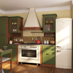 Холодильник белого цвета в интерьере кухни с зеленым гарнитуром