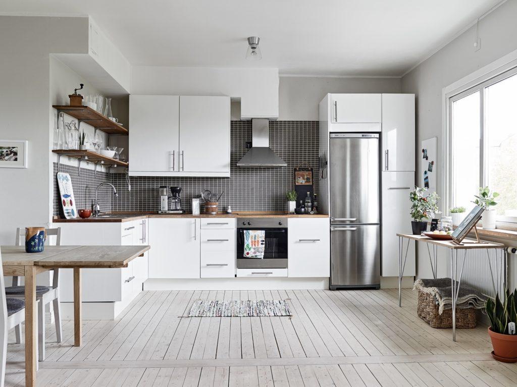 Холодильник серебристого цвета в интерьере белой кухни