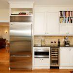 Холодильник в интерьере белой кухни угловой.