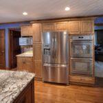 Холодильник в интерьере кухни в бежевом гарнитуре