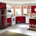 Холодильник в интерьере кухни в красных тонах