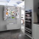 Холодильник в интерьере кухни в светло-сером шкафу