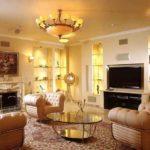 Оформление гостиной комнаты с кожаными креслами и журнальным столиком из стекла