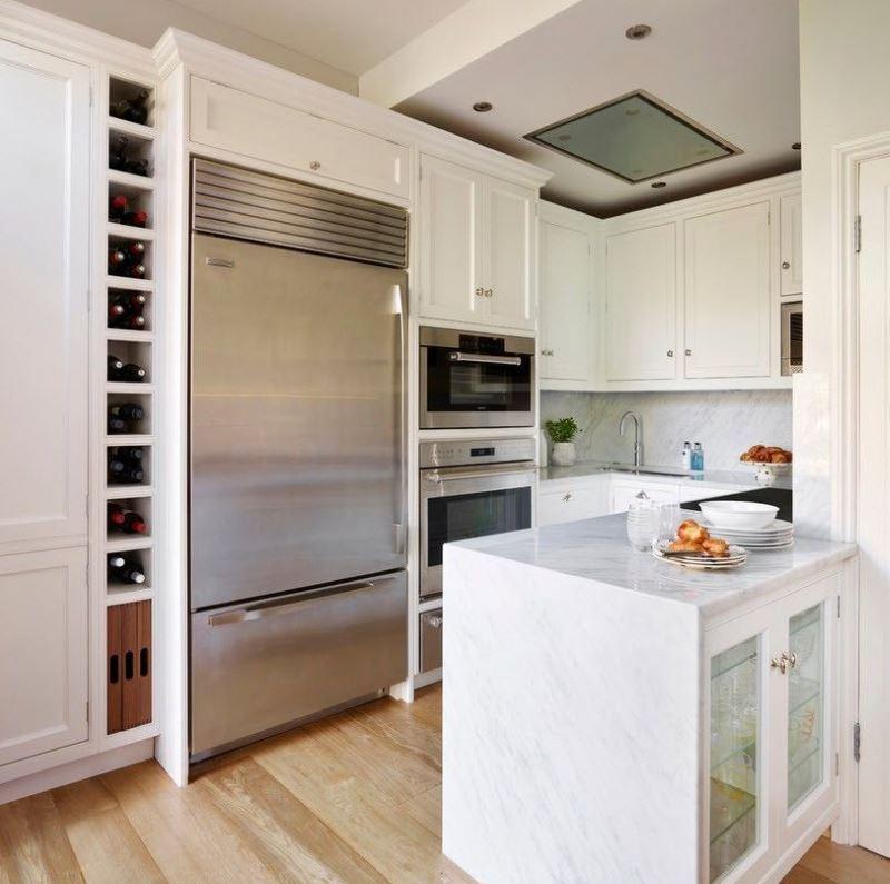 Белый кухонный гарнитур и холодильник с отделкой из нержавеющей стали