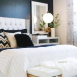 Белая кровать на фоне черной стены