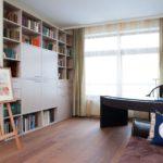 Мольберт и книжные стеллажи в комнате творческой девушки