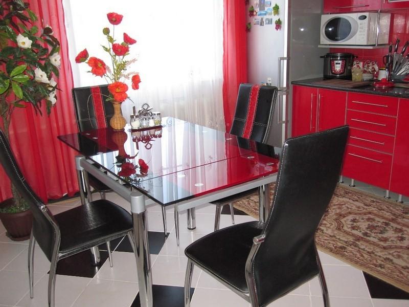 Черные стулья около кухонного стола со столешницей из закаленного стекла
