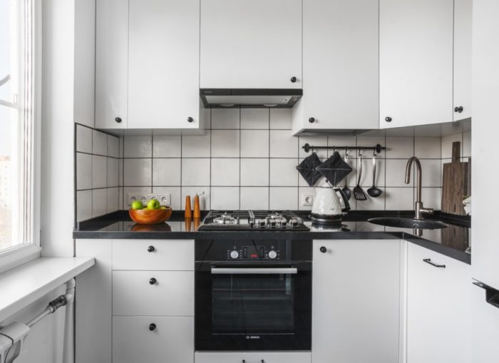 Черная духовка в белом кухонном гарнитуре