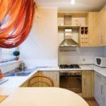 Красные шторы на кухне с мойкой в подоконнике